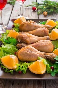 Fried chicken legs with lettuce and oranges on a plate close-up.