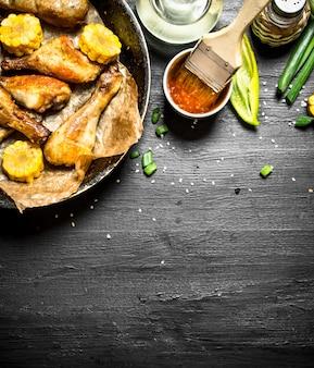 Жареные куриные окорочка с кусочками кукурузы и томатным соусом.