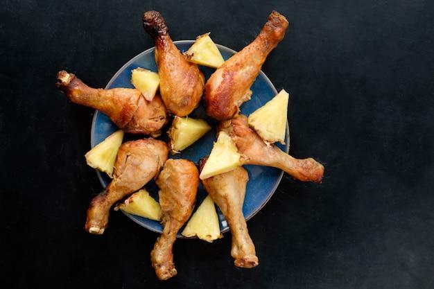 黒いテーブルの表面に青い皿にパイナップルの部分とフライドチキンの足