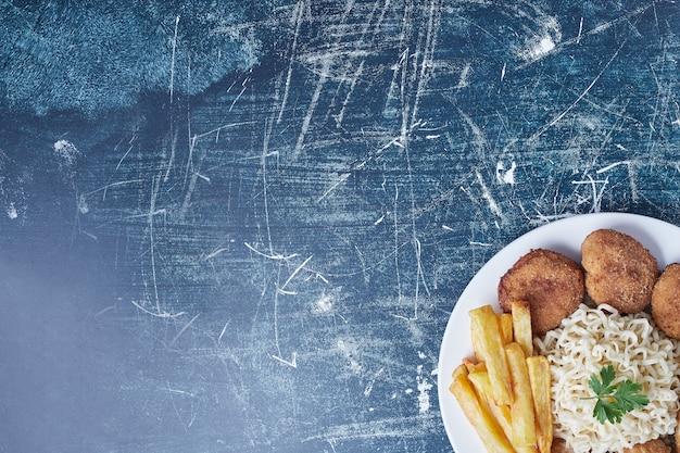 감자와 파스타를 곁들인 프라이드 치킨 다리.