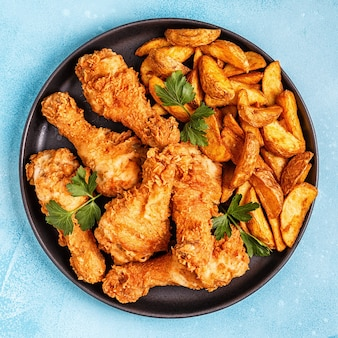 Fried chicken legs with potatoes. top view