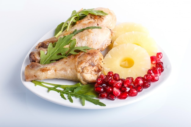 Fried chicken legs with rucola pineapple and pomegranate seeds isolated on white background