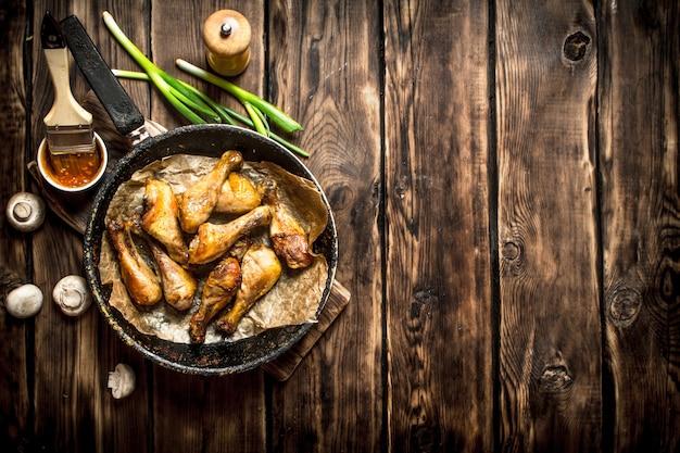 Жареные куриные ножки с томатным соусом на деревянном столе