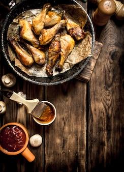 Жареные куриные ножки в томатном соусе. на деревянном столе.