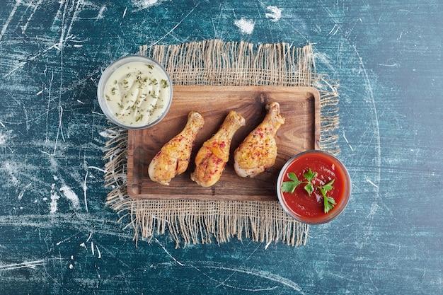 Cosce di pollo fritte su una tavola di legno con salse.