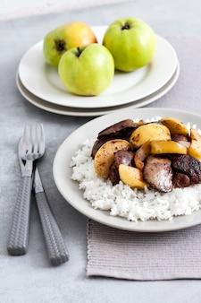 사과와 함께 튀긴 닭 간은 접시에 흰 쌀과 함께 제공됩니다. 배경에 녹색 사과