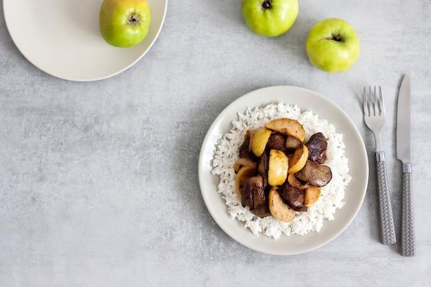 Жареная куриная печень с яблоками подается с белым рисом на тарелке.