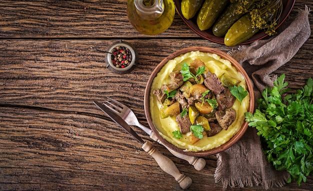 Жареная куриная печень с яблоками, сладким перцем и луком с картофельным пюре как крупный план в миску на деревянный стол. вид сверху. квартира лежала.