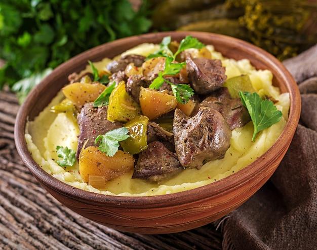 Жареная куриная печень с яблоками, сладким перцем и луком с картофельным пюре как крупный план в миску на деревянный стол.