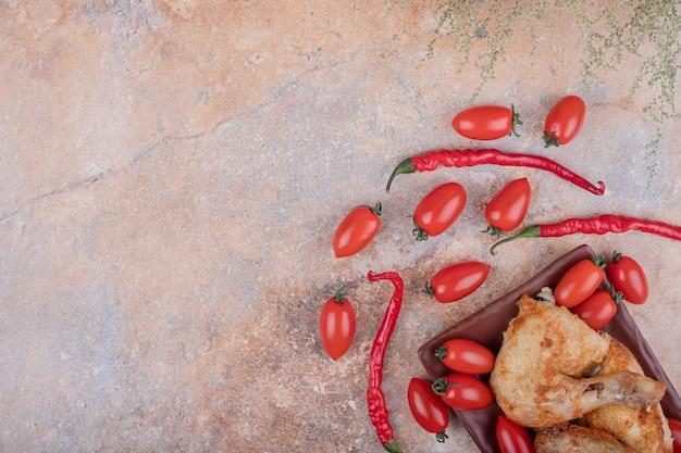 Pollo fritto in un piatto di ceramica con peperoncini e pomodorini.