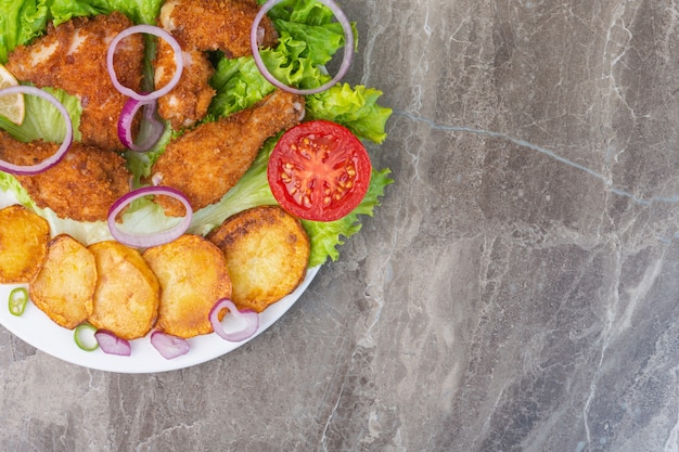 Fried chicken meat, potatoes and vegetables on a plate, on the marble background.