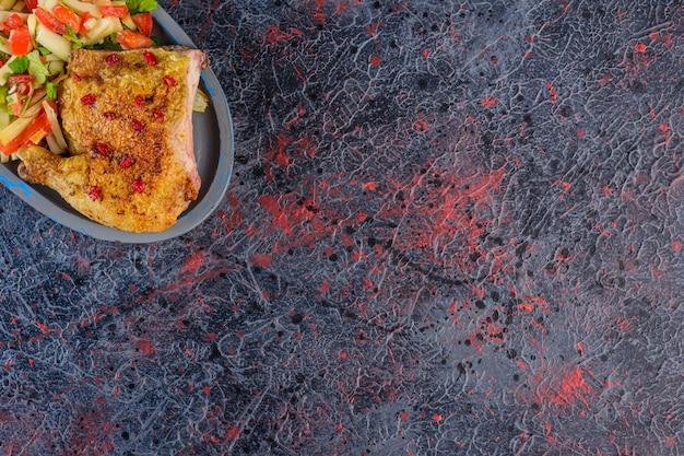 어두운 표면에 혼합 야채 샐러드와 튀긴 닭고기