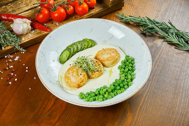 Fried chicken meatballs (cutlets) garnished with peas, mashed potatoes and cucumber in a white bowl on a wooden table. tasty and healthy diet food. close up view.