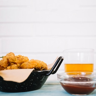 Жареная курица возле пива и кетчупа