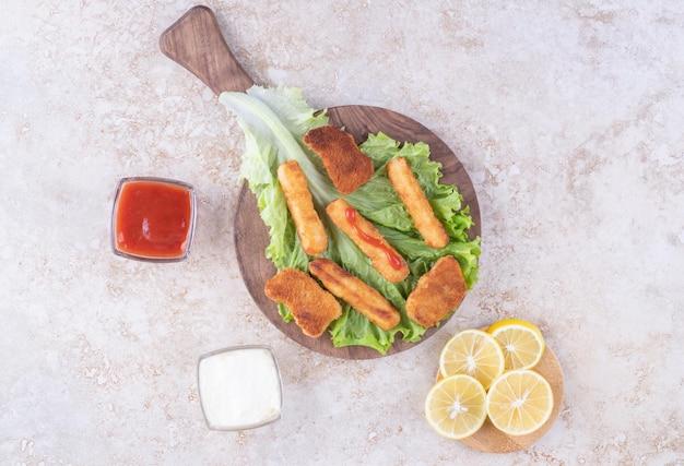Жареные куриные наггетсы и палочки из колбасы на гриле на листе салата с соусами вокруг.