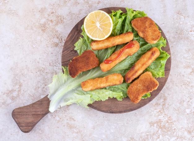 Bocconcini di pollo fritto e bastoncini di formaggio su una tavola di legno su un pezzo di foglia di lattuga.