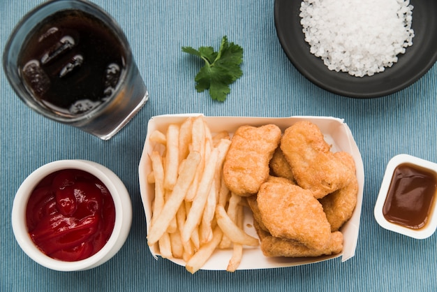 Fried chicken nuggets; french fries; tomato sauce; coriander; soft drink on table