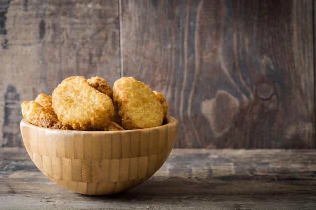 Жареные куриные наггетсы в миске на деревянном столе