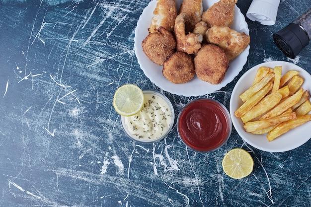 Bocconcini di pollo fritto, gambe e patate con salse, vista dall'alto.