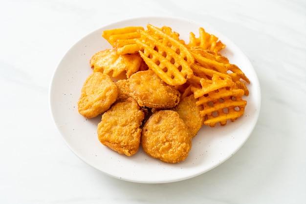 접시에 튀긴 된 감자와 프라이드 치킨 너 겟