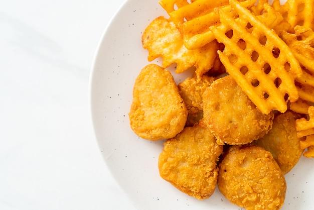 Жареные куриные наггетсы с жареным картофелем на тарелке