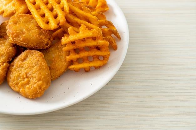 접시에 튀긴 감자와 프라이드 치킨 너겟