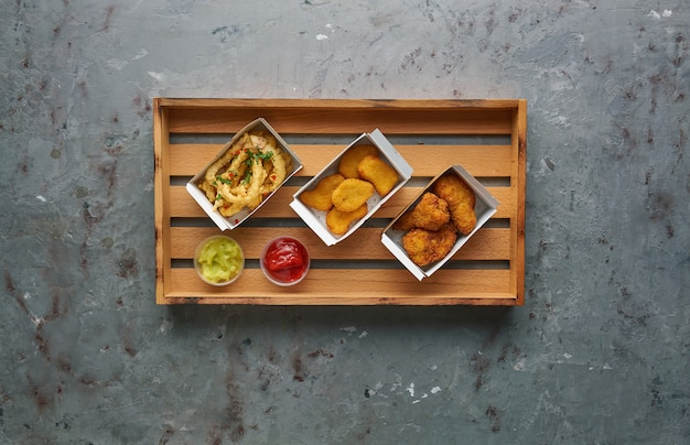 足とシャキッとしたタコと木製のトレイ、上面図、コピースペースのフライドチキンナゲット。屋台の食べ物のコンセプト