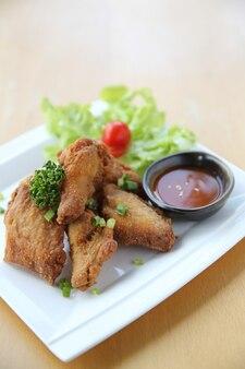 Жареный цыпленок на деревянном фоне