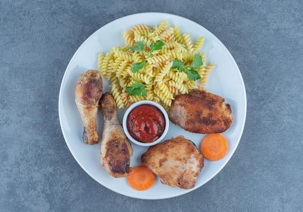 Жареные куриные части и фузилли на белой тарелке.