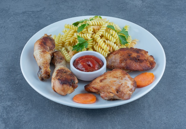 Fried chicken parts and fusilli on white plate.
