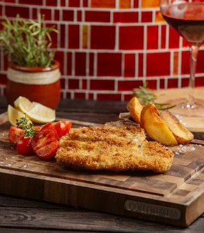 Fried chicken patties served with fried potatoes, lemon and tomato on wood board