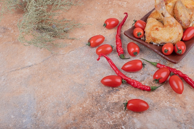 핫 칠리 페퍼와 체리 토마토를 곁들인 프라이드 치킨 조각.