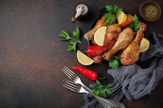 Жареные куриные ножки на чугунной сковороде на темном бетонном или каменном фоне