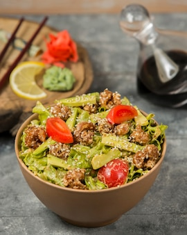 Fried chicken salad with fresh avocado, lettuce, tomato in oil garnished with sesame