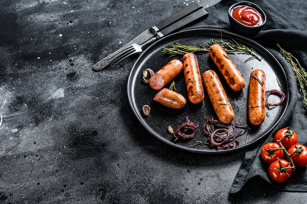 Fried chicken sausages with onion, garlic and rosemary. black background