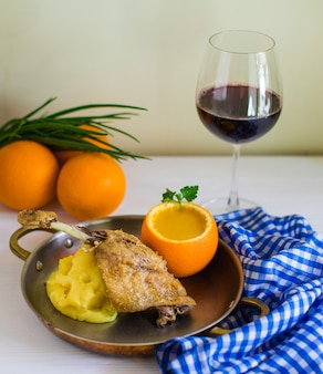 Fried chicken served with mashed potato and lentil soup in orange skin bowl