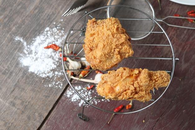 Fried chicken on sieve,  powder on wood floor