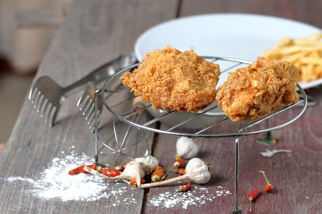Fried chicken on sieve, powder on wooden floor background.