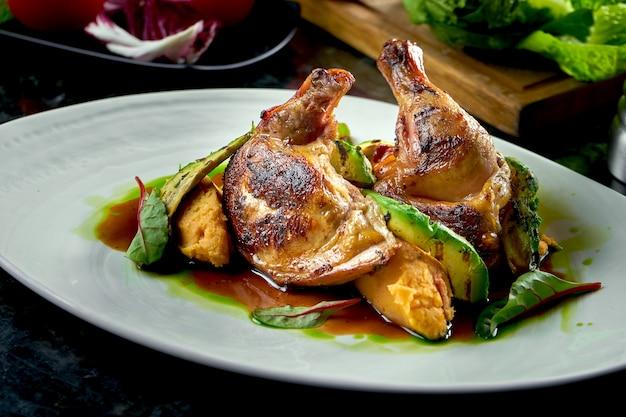 Жареные куриные бедра с желто-зеленым соусом, украшенные картофельным пюре и авакодо, подаются на белой тарелке. ресторанная еда. мясное блюдо Premium Фотографии