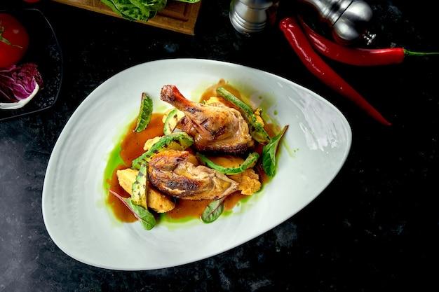 Жареные куриные бедра с желто-зеленым соусом, украшенные картофельным пюре и авакодо, подаются на белой тарелке. ресторанная еда. мясное блюдо