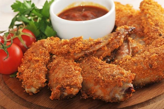 Жареные куриные крылышки в панировке с кетчупом, помидорами и петрушкой