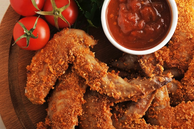 Fried chicken wings breaded with ketchup, tomato and parsley
