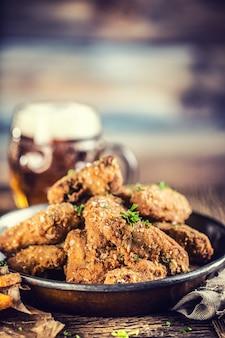 펍이나 레스토랑의 테이블에 프라이드 치킨 윙 프라이와 생맥주.