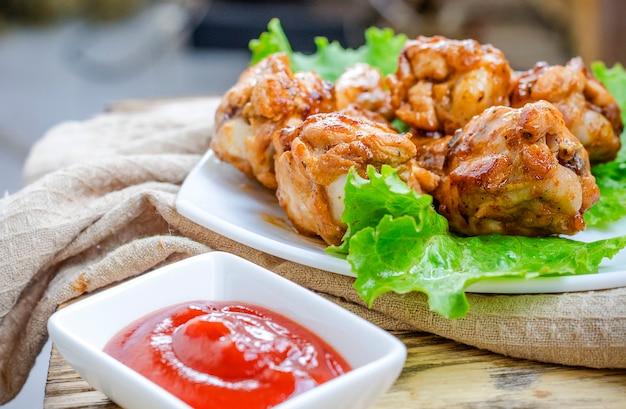 Жареные куриные крылышки на тарелке и соусе