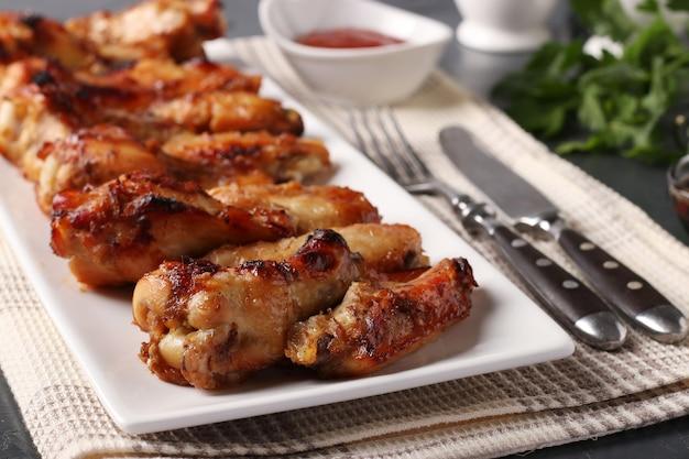 Жареные куриные крылышки на белой тарелке, подаются с томатным соусом, крупный план, горизонтальный формат