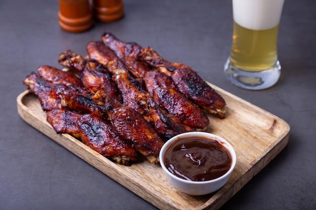 Жареные куриные крылышки на деревянной доске с соусом барбекю и бокалом пива.