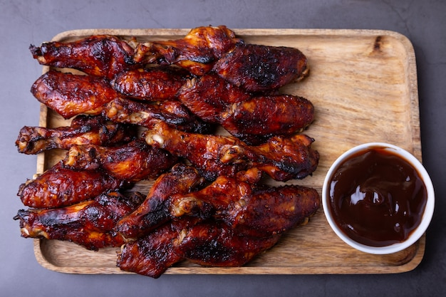 Жареные куриные крылышки на деревянной доске с соусом барбекю.