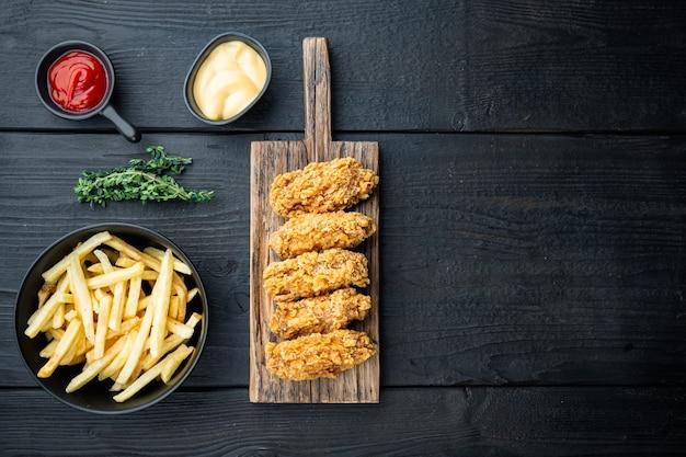 검은 나무 테이블에 튀긴 닭 날개 부품
