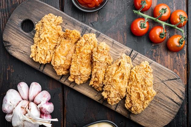 오래 된 어두운 나무 테이블에 튀긴 닭 날개 부품