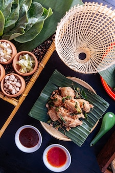 Fried chicken wings in thai northeastern style with garlic and kaffir lime leaves.